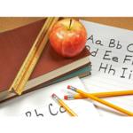 Schulbücher, Stifte und Apfel